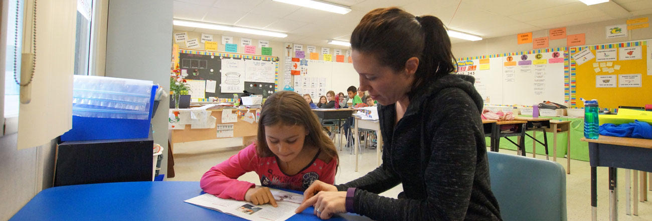 Parent volunteer reading with student
